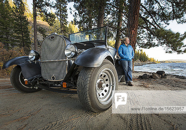 Woman standing next to renovated truck watching sunset along sheltered beach on Payette Lake in McCall  Idaho