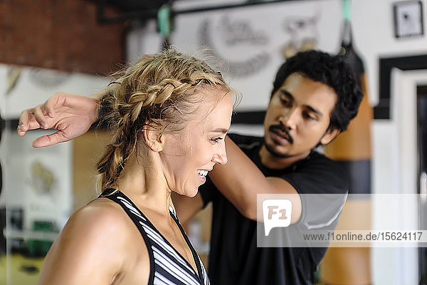 Photograph of young woman getting assistance stretching from trainer in gym  Seminyak  Bali  Indonesia
