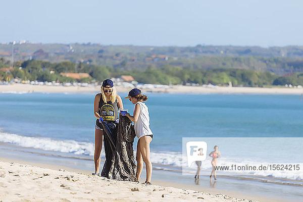 Two young women picking up trash at beach  Jimbaran  Bali  Indonesia