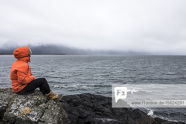 Professional Snowboarder Robin Van Gyn sits on a rock and looks over the ocean on a stormy down day while on snowboard trip to Haines  Alaska.