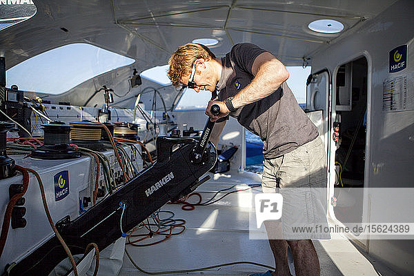 Sailor maneuvering on winch inside cockpit of trimaran  Atlantic Ocean  Brittany  France