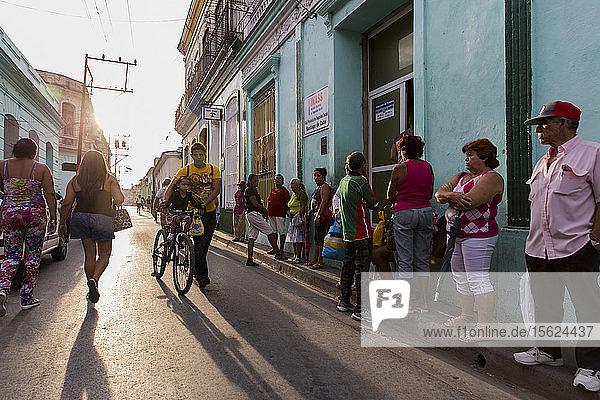 People walking and standing on city street at dawn  Santiago de Cuba  Cuba