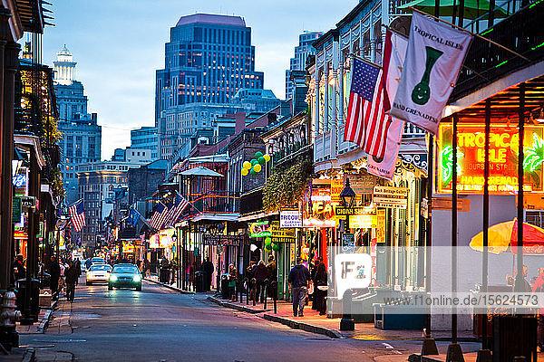 Bourbon Street lights up at dusk in New Orleans  Louisiana.