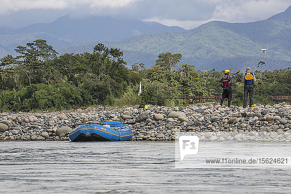 Photograph with rear view of two men watching drone fly while stopping from rafting down jungle river in Manu National Park  Peru
