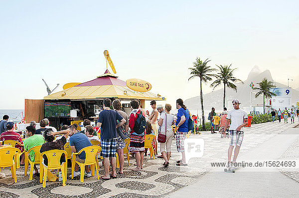 Crowd Watching A Soccer Game On Television With Skateboarder Passing By On The Ipanema Beach