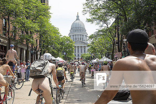 Large number of naked cyclists riding toward state capitol to protest dependence on fossil fuels  Madison  Wisconsin  USA