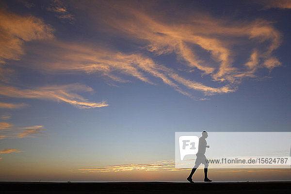 A person jogs as the sun sets at Windansea Beach in the La Jolla neighborhood of San Diego  California.