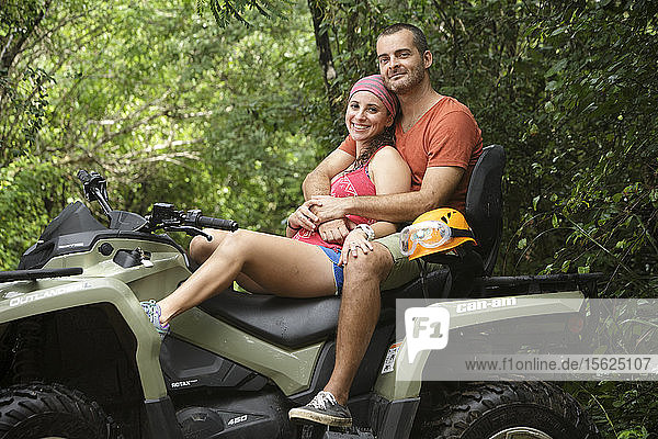 Couple smiling and embracing while sitting on quad bike in Emotions Native Park  Quintana Roo  Mexico