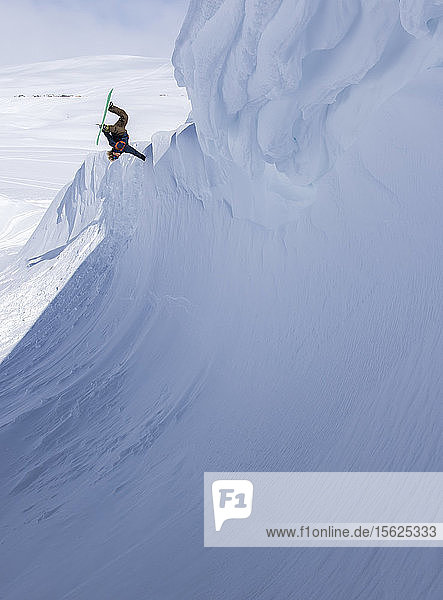 Snowboarder Doing Handplant On Quarter Pipe Like Feature On Sunny Winter Day