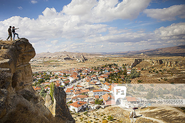 Two hikers over looking Cavusin  an old Greek village in Cappadocia Turkey. It has a 5th century church of Saint John  and a marvelous view into the Rose and Red Valleys.