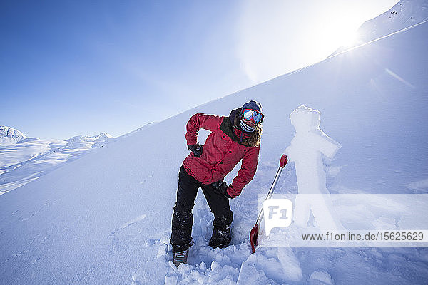Professional Snowboarder Marie France Roy  hangs out with a snow man carved from the hard wind layer on the surface on a sunny day in Haines  Alaska.