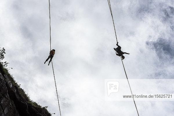 Blick von unten auf zwei abenteuerlustige Slackliner  Steinbruch Dibs  Maripora  Staat Sao Paulo  Brasilien
