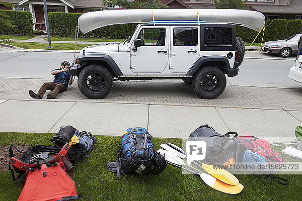 An Adventurer Ties His Canoe To The Roof Of His Jeep In Preparation For A Paddling Trip