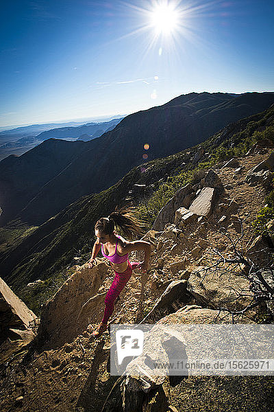 A girl in athletic wear runs down a rocky section of the Pacific Crest Trail.