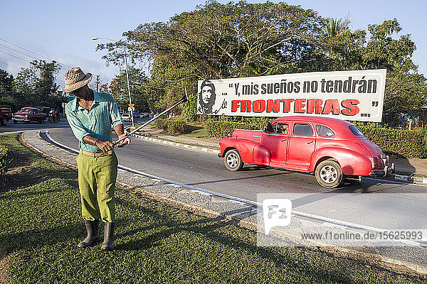 Full length shot of man cutting lawn on roadside  Pinar del Rio  Cuba