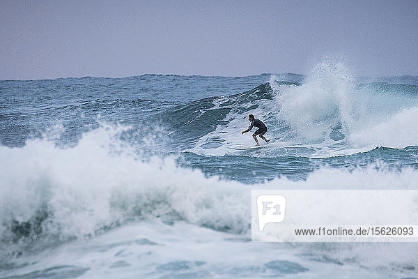 Man surfing at dusk on messy waves on North Shore of Oahu  Hawaii  USA