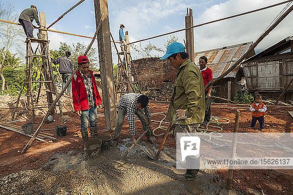 Männer bauen ein neues Haus mit modernen Materialien in Boun Neua  Provinz Phongsaly  Laos  während ein kleines Mädchen zusieht.