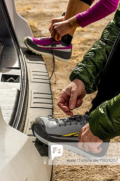 Man and woman putting on shoes for a trail run