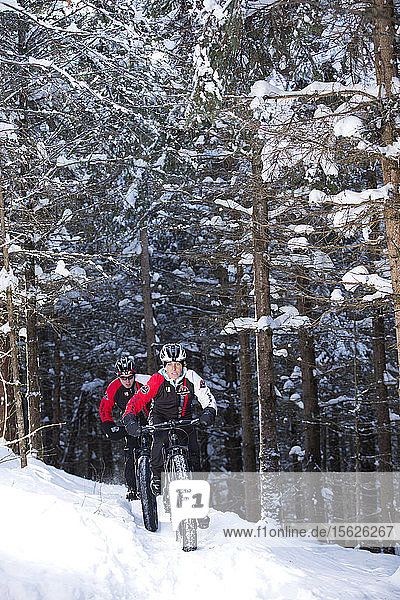 Rocky Mountain professional bikers during winter training session on Fat Bike in mountain trail of Quebec  Canada