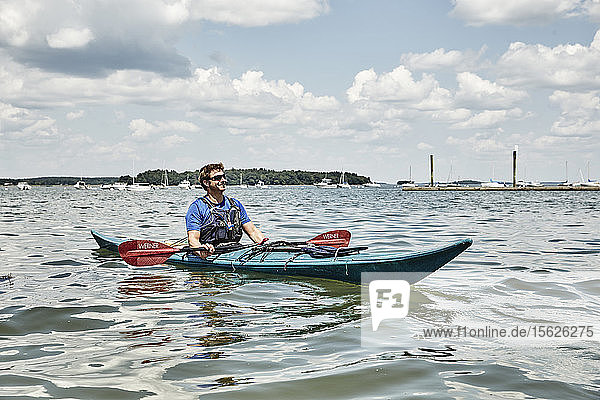 White clouds over man kayaking against sailing boats  Portland  Maine  USA