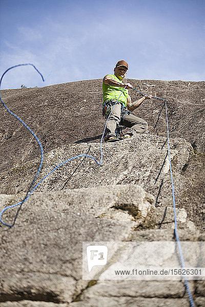 Kletterer befestigt Seil zum Abseilen