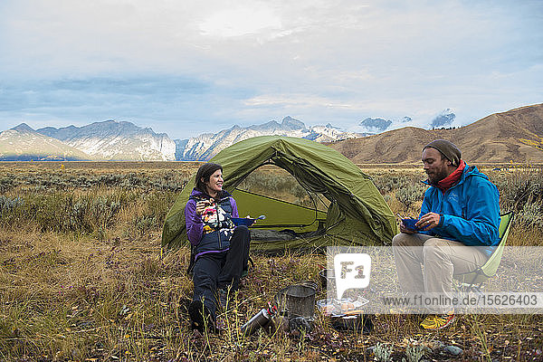 Couple eating while camping in front of tent with mountains of Teton Range in background  Jackson  Wyoming  USA