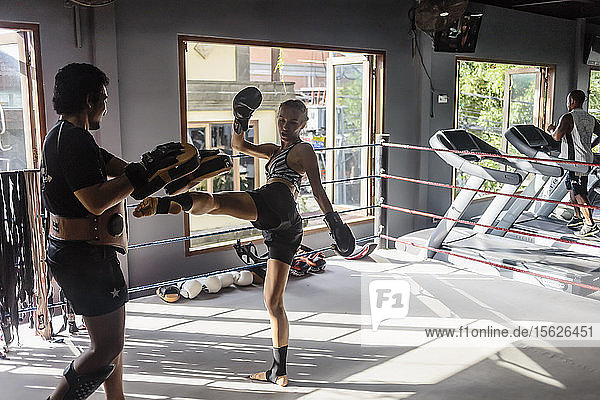 Photograph of young woman kicking while practicing kickboxing with coach  Seminyak  Bali  Indonesia