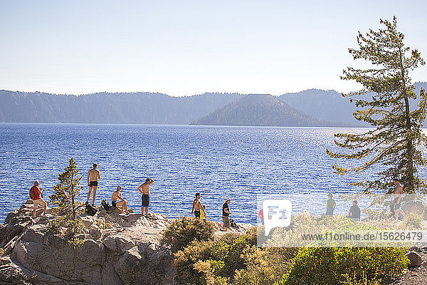 Young people wait on a rock outcrop and swim or jump into the deep blue waters of Crater Lake  Oregon  USA