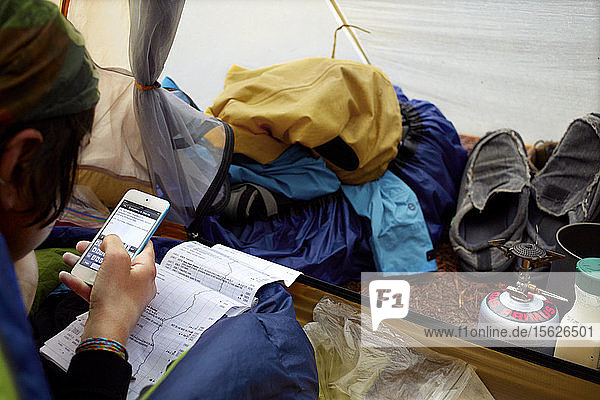 An Appalachian Trail thru hiker records notes about her journey in her tent while waiting for morning rain to pass.