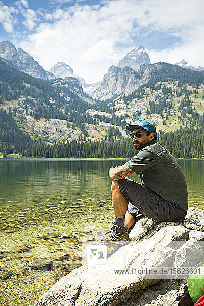 A Backpacker Sitting On Rock At A Lake Of The Grand Teton Mountains In Jackson Hole  Wyoming