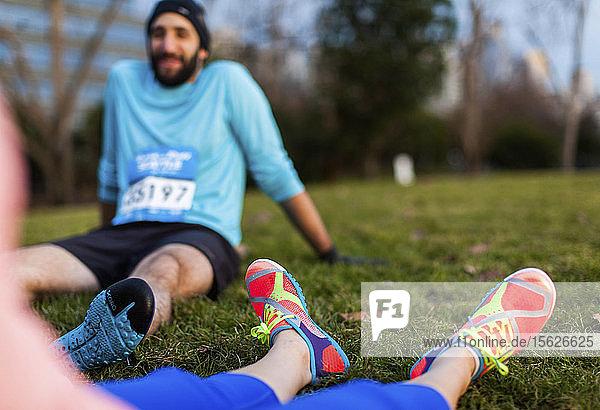 Two runners taking break sitting on grass  Seattle  Washington State  USA