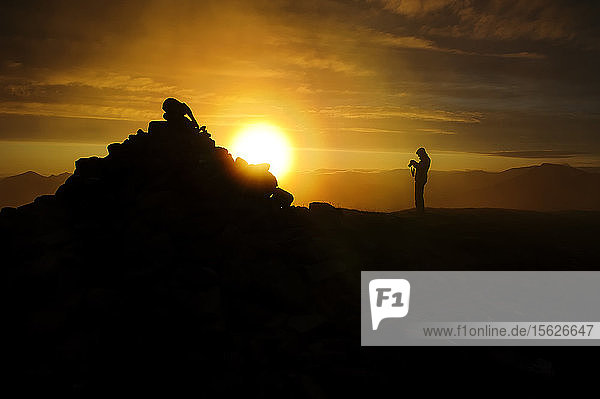 A silhouette of a hiker  photographer at the summit of The Suilven mountain in Scotland  United Kingdom.