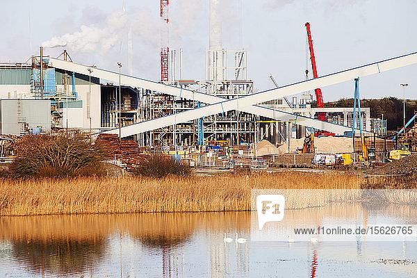 Die Iggesund-Papierfabrik in Workington  Cumbria  Vereinigtes Königreich  mit einer Windturbine  die das Werk mit Strom versorgt  und mit Bauarbeiten für ein neues Biokraftstoff-Kraftwerk  das die Produktionsanlage mit Strom versorgt.