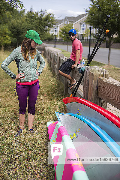 Man And Woman Looking At Paddleboards Near Wooden Railing In New York City