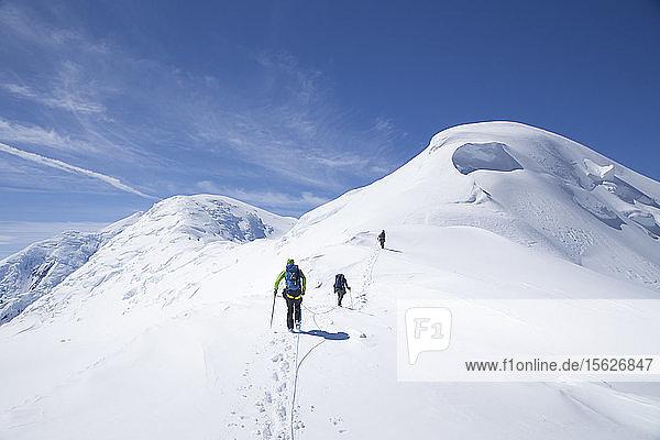 Bergsteiger auf dem Weg zum Gipfel des Kahiltna Dome  einem Berg in der Nähe des Denali in Alaska. Die Bergsteiger sind mit einem Seil verbunden  um sie vor dem Absturz in eine Gletscherspalte zu schützen. Der Denali-Nationalpark ist ein großartiger Ort für Skitouren und Bergsteiger-Touren im Hinterland.