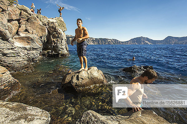 Young people wait on a rock outcrop and swim or jump into the deep blue waters of a mountain lake,  Crater Lake,  Oregon,  USA