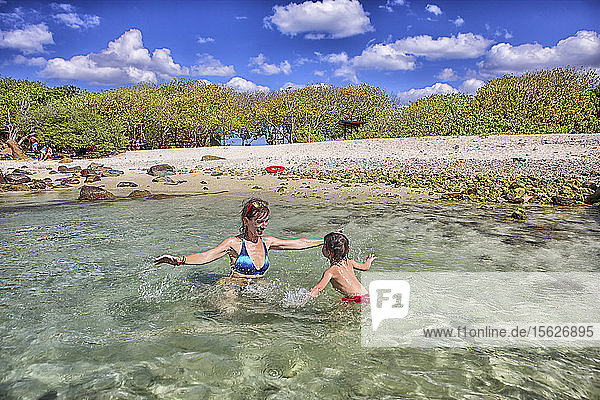 Mother and daughter playing in the sea. Pigeon Island. Sri Lanka