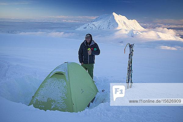 Ein Skitourengeher genießt die abendliche Aussicht auf den Mount Hunter  während er neben seinem Zelt im 14.000-Fuß-Camp auf dem Gletscher des Denali steht.