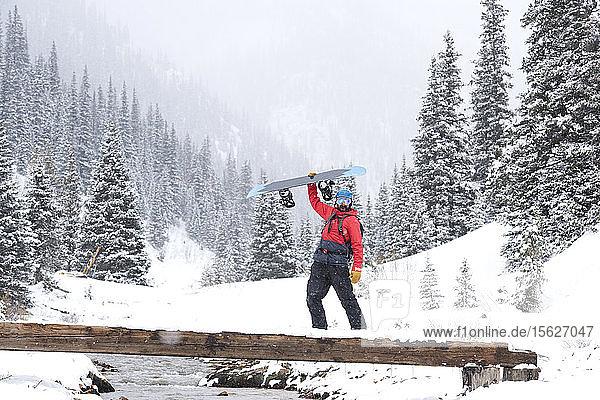 Ein Snowboarder hält sein Brett  während er über eine Fußgängerbrücke geht