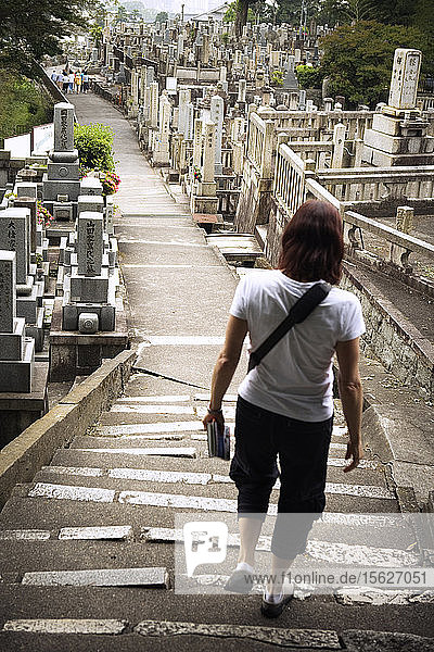 Rear view of a woman walking down the steps in a cemetery in Kyoto,  Japan.
