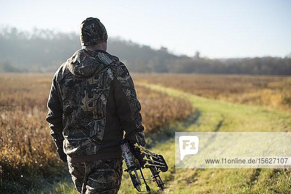 Junger erwachsener männlicher Jäger  der während der Bogensaison in einem Feld nach Rehen Ausschau hält