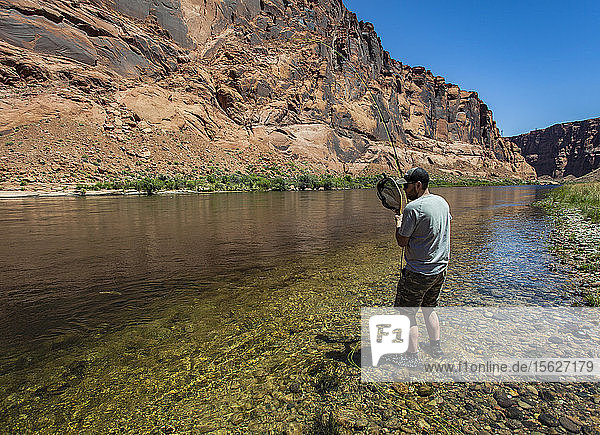 Man Reels In Fish On The Colorado River In The Grand Canyon