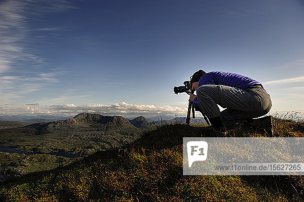 A male photographer taking pictures from a mountain summit at The Suilven  Scotland  United Kingdom.