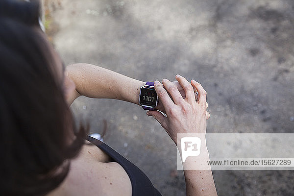 Woman checking her Fit Bit fitness tracker watch on her wrist.