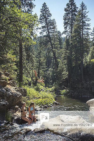 Blick auf zwei junge Frauen  die auf einem Felsen im Fluss sitzen  und einen Mann  der von einer Klippe springt  McCloud River  Kalifornien  USA