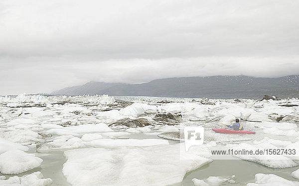 Männlicher Kajakfahrer navigiert auf dem Eis des Lowell Lake