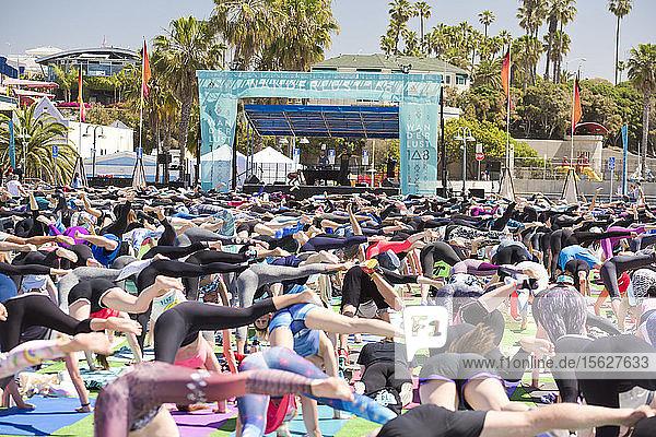 Menschen  die während des Yoga-Festivals auf dem Santa Monica Pier in Santa Monica  Kalifornien  USA  die einbeinige Hundehaltung einnehmen