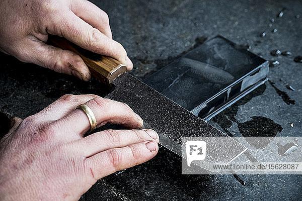 Hochwinkel-Nahaufnahme einer Person,  die ein handgefertigtes Messer auf einem Schleifstein schleift.