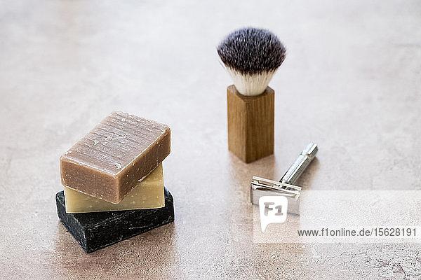 Nahaufnahme von drei hausgemachten Seifenstücken  Rasierpinsel und Rasierapparat aus einem hohen Winkel. Nahaufnahme von drei hausgemachten Seifenstücken, Rasierpinsel und Rasierapparat aus einem hohen Winkel.