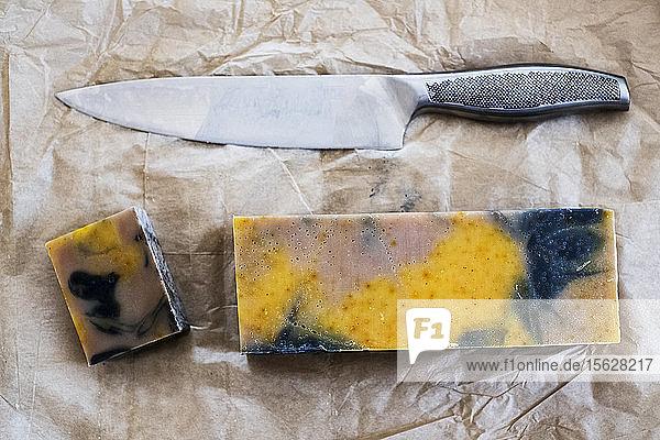 Nahaufnahme von gelben und schwarzen hausgemachten Seifenstücken und Küchenmessern in einem hohen Winkel. Nahaufnahme von gelben und schwarzen hausgemachten Seifenstücken und Küchenmessern in einem hohen Winkel.